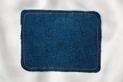 文本的框架从与橙色螺纹的被缝的线的一种蓝色牛仔裤织品 免版税库存图片