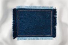 文本的框架从与被装饰橙色螺纹的被缝的线的一种蓝色牛仔裤织品和 库存图片