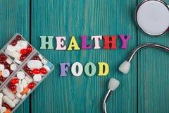 文本& x22; 健康food& x22;色的木信件、听诊器和药片 库存图片
