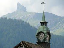 文根,瑞士 山和教会有时钟的 库存照片