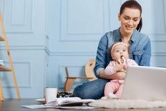 读文章的吸引人年轻妈妈在父母身分 库存图片