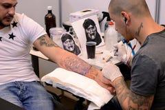 文身的人在他的2015年4月18日,索非亚,保加利亚的客户的做纹身花刺 免版税库存照片