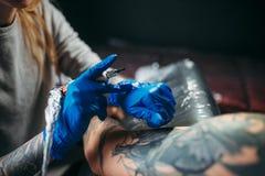 文身的人由机器做纹身花刺在男性肩膀 库存照片