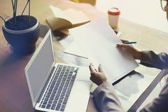 文件在顶楼办公室裱糊板料,研究便携式计算机 队工作,商人 设计版面的空间 免版税库存照片