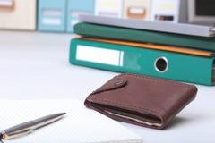 文件夹文件、笔记和钱包在书桌上 被弄脏的背景 库存图片