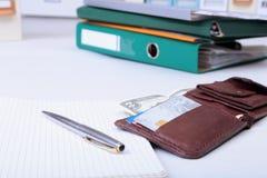 文件夹文件、笔记和钱包在书桌上 被弄脏的背景 免版税库存照片