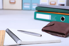 文件夹文件、笔记和钱包在书桌上 被弄脏的背景 库存照片
