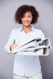 给文件夹的愉快的美国黑人的妇女在照相机 库存照片