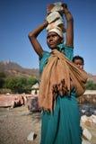 斋浦尔,印度, 2017年12月1日:工作艰苦carring的妇女向佩带后面的孩子扔石头 库存图片