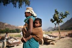 斋浦尔,印度, 2017年12月1日:工作艰苦carring的妇女向佩带后面的孩子扔石头 库存照片