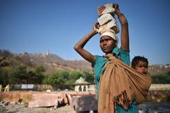 斋浦尔,印度, 2017年12月1日:工作艰苦carring的妇女向佩带后面的孩子扔石头 免版税库存图片