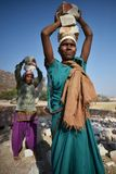 斋浦尔,印度, 2017年12月1日:工作艰苦carring的妇女向佩带后面的孩子扔石头 免版税库存照片
