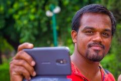 斋浦尔,印度- 2017年9月19日:一个印地安人的画象在手上的拿着他的手机在德里红堡在德里 免版税库存图片