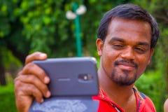 斋浦尔,印度- 2017年9月19日:一个印地安人的画象在手上的拿着他的手机在德里红堡在德里 免版税库存照片