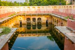 斋浦尔,印度- 2017年9月20日:古庙在水, Galta ji寺庙斋浦尔拉贾斯坦中反射了 库存照片