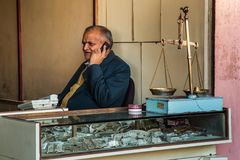 斋浦尔,印度- 2018年1月10日:在柜台后的首饰客商 他在电话谈话 库存图片