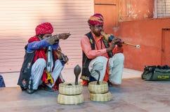 斋浦尔,印度- 2014年12月29日:耍蛇者演奏眼镜蛇的长笛在风宫殿前面 免版税图库摄影