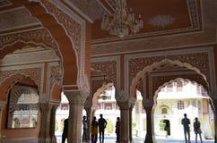 斋浦尔,拉贾斯坦,印度:城市宫殿俏丽的内部在斋浦尔印度,享受宫殿的建筑学的游人 免版税库存图片