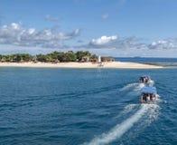 斐济岛最佳的海滩照片 有森林的海岛和村庄,有小船的自然全景有蓝色屋顶的 免版税库存照片