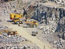 翻斗车和挖掘机在花岗岩挖掘 免版税图库摄影