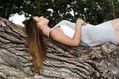 斜倚在树外形的可爱的白种人青少年的女孩 库存照片