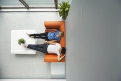 斜倚在橙色沙发的两个人在办公室 免版税库存照片