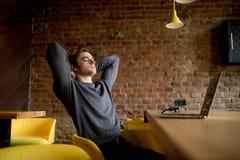 斜倚在膝上型计算机的大厅的轻松的成熟商人 免版税库存照片