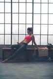 斜倚在长凳的妇女选择在顶楼健身房的音乐 免版税库存图片