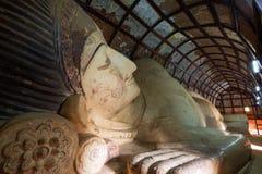 斜倚的菩萨巨大的雕象在一个寺庙里面的在Bagan 免版税图库摄影
