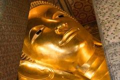 斜倚的菩萨金雕象面孔。Wat Pho,曼谷,泰国 免版税库存图片