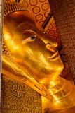 斜倚的菩萨金雕象面孔在曼谷,泰国 库存照片