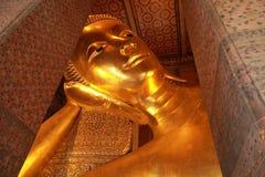 斜倚的菩萨金雕象面孔,泰国 免版税库存图片