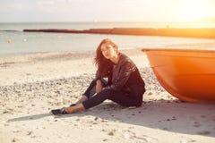 斜向一边女孩在海滩的一条红色小船附近由海 库存照片