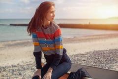 斜向一边女孩在海滩的一条红色小船附近由海 免版税图库摄影
