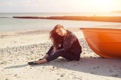 斜向一边女孩在海滩的一条红色小船附近由海 免版税库存图片