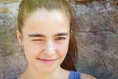 斜眼看一只眼睛的微笑的十几岁的女孩 库存图片