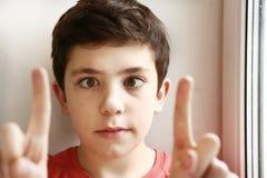 斜眼看把戏的青春期前的英俊的男孩戏剧 库存照片