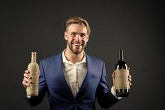 斟酒服务员举行两瓶酒 专业酒degustation概念 有酒瓶的人正装在手上 免版税库存照片