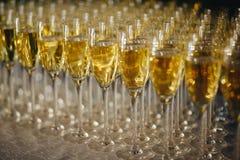 斟酒服务员倒从瓶的香槟入玻璃在桌上在餐馆 免版税库存图片