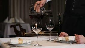 斟酒服务员倒红葡萄酒入从蒸馏瓶的一块玻璃 股票视频