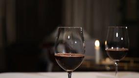 斟酒服务员倒红葡萄酒入从蒸馏瓶的一块玻璃 股票录像