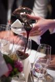 斟酒服务员倾吐的酒到从混料盆,豪华吃饭的客人的玻璃里 图库摄影