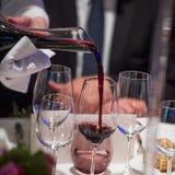 斟酒服务员倾吐的酒到从混料盆,豪华吃饭的客人的玻璃里 库存图片
