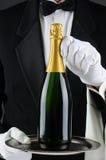 斟酒服务员藏品在盘的香宾瓶 图库摄影
