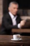断裂时间。读与杯子的成熟商人一张报纸  库存照片