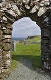 斯凯岛,苏格兰-看法小岛通过被破坏的Trumpan教会拱道横跨一个绿色象草的坟园的往遥远的海c 库存图片