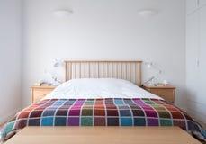 斯坎迪样式卧室内部与木卧室家具、白色被绘的墙壁、白色卧具和五颜六色的毯子 免版税库存照片