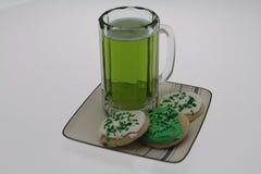 斯坦用绿色啤酒和被冰的一种油脂含量较高的酥饼在一块板材为圣帕特里克` s天 免版税库存图片