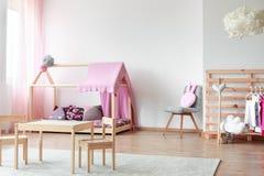 斯堪的纳维亚样式女孩` s卧室 免版税库存照片