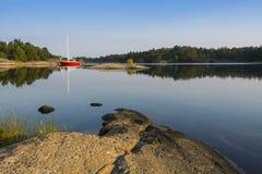 斯德哥尔摩群岛:被停泊的红色sailingboat在自然港口 免版税库存照片